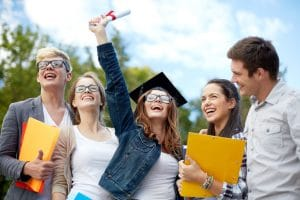 Education, graduation and people concept - group of smiling students in mortarboard with diploma and school folders