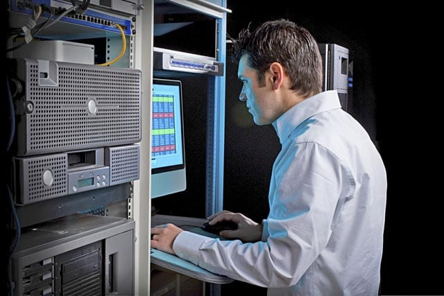 An IT technician working at a computer monitor in equipment room.