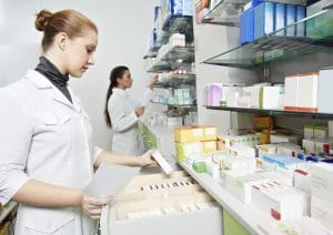 Two pharmacy technicians working in pharmacy drugstore.