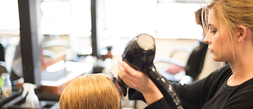 An IntelliTec College Cosmetology student practices her hair styling skills