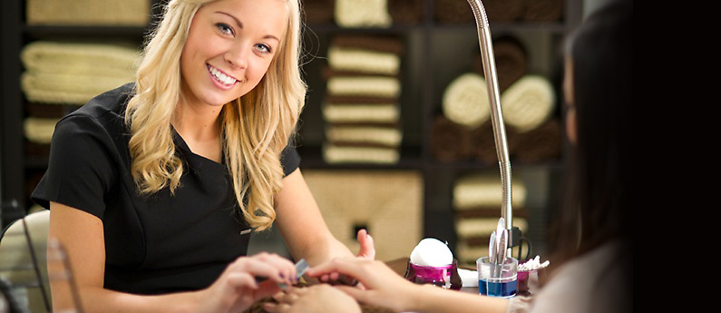 A young blonde woman is smiling at the camera while doing a manicure on another woman's hand