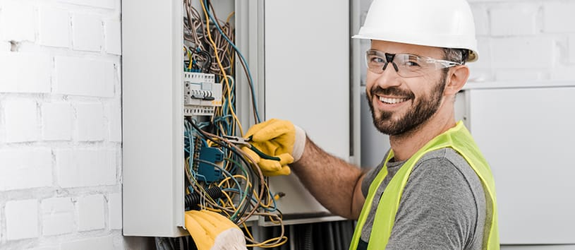 Male electrical technician working on a wire box.